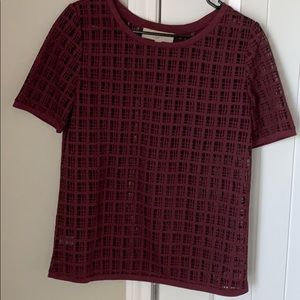 Plum colored, textured short sleeve shirt.